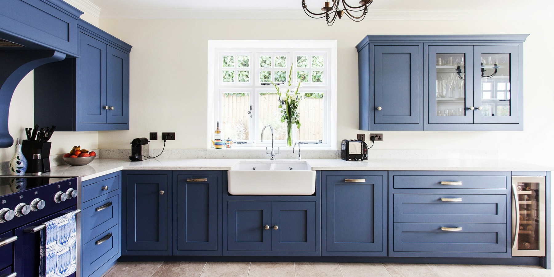Bespoke Blue Galley Style Shaker Kitchen - Burlanes handmade Wellsdown kitchen with silver cup handles, a double Belfast sink and white worktops.