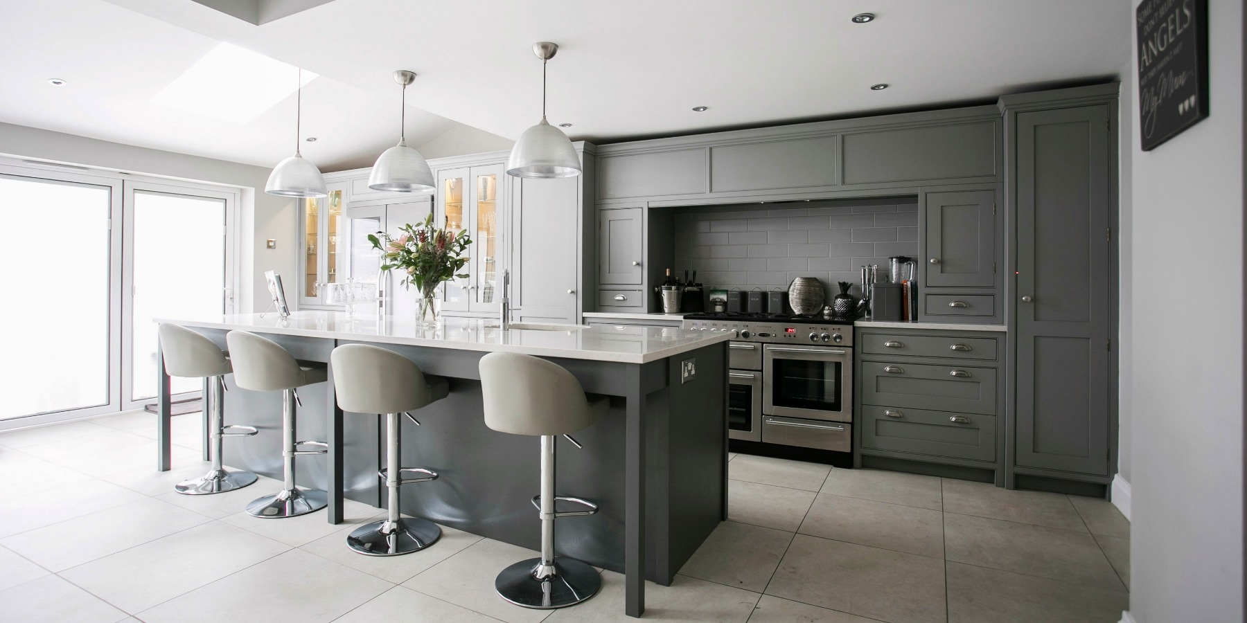 Luxury Shaker Kitchen - Burlanes bespoke grey Wellsdown kitchen with white worktops, glass cabinets and pendant lights.