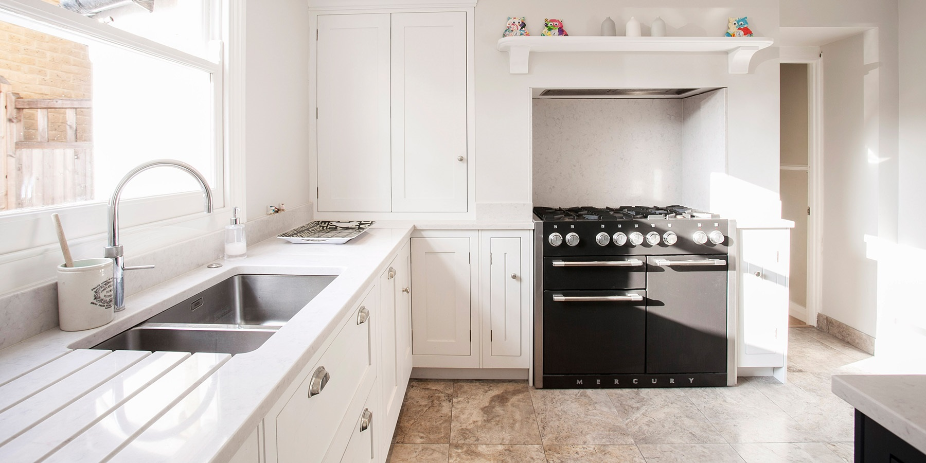 Handmade White Shaker Kitchen - Burlanes bespoke Hoyden kitchen cabinetry in white with white worktops, stainless steel sink and black Mercury range oven.