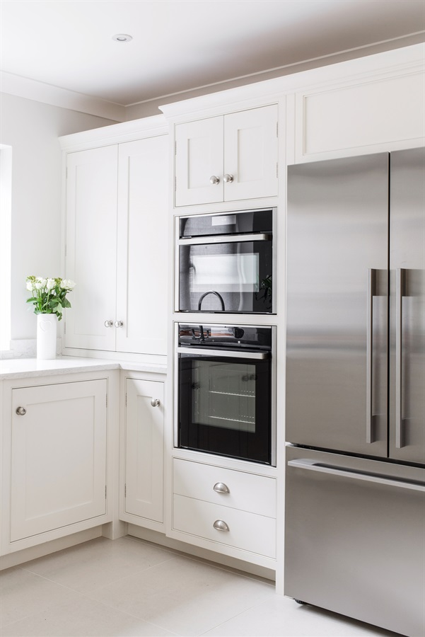 Bespoke White Shaker Kitchen - Burlanes handmade Wellsdown kitchen with white worktops, and bespoke refrigerator surround.
