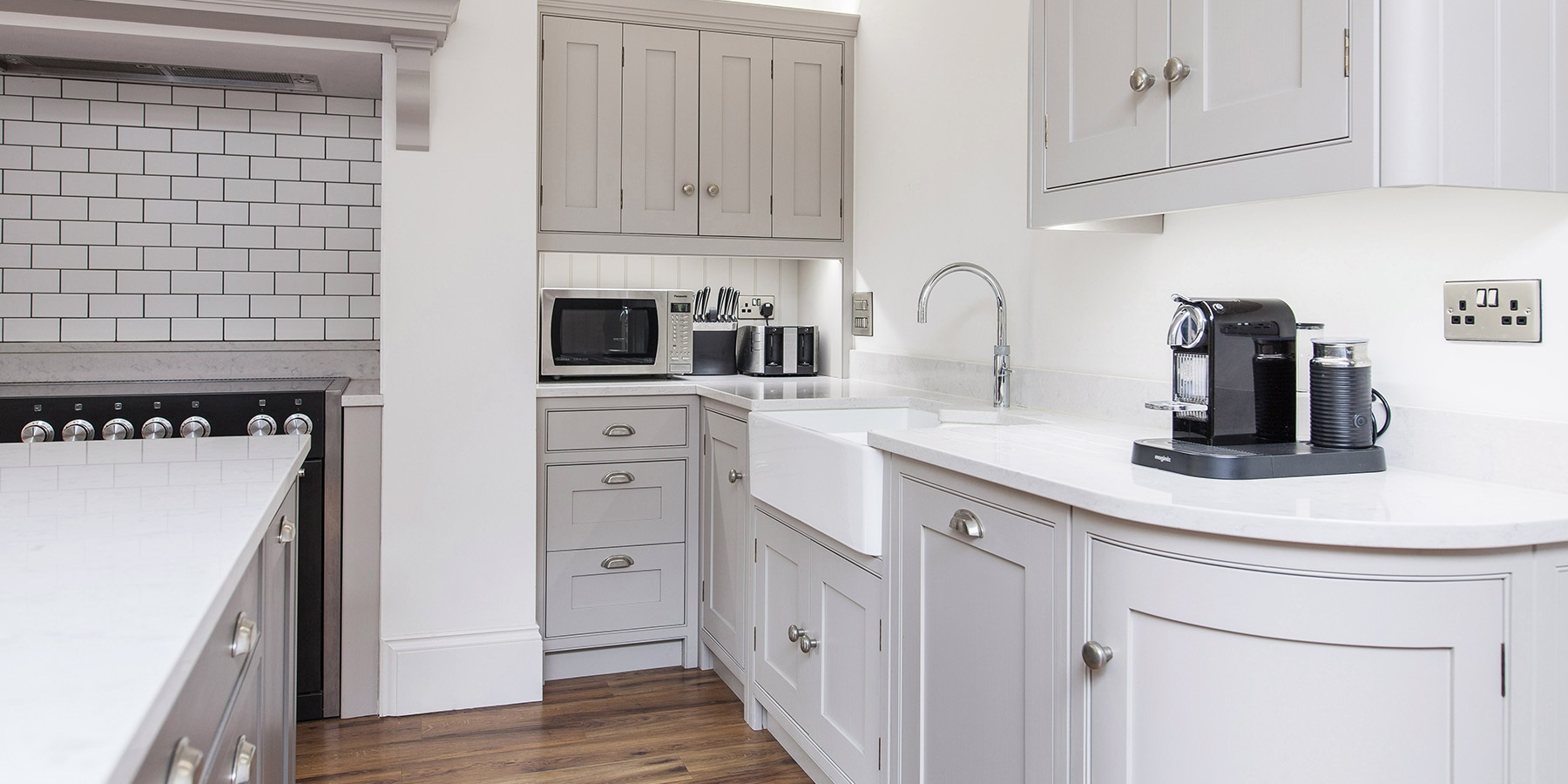 Bespoke Shaker Kitchen - Burlanes handmade grey Wellsdown kitchen with white worktops, double Belfast sink and white metro splashback tiles.