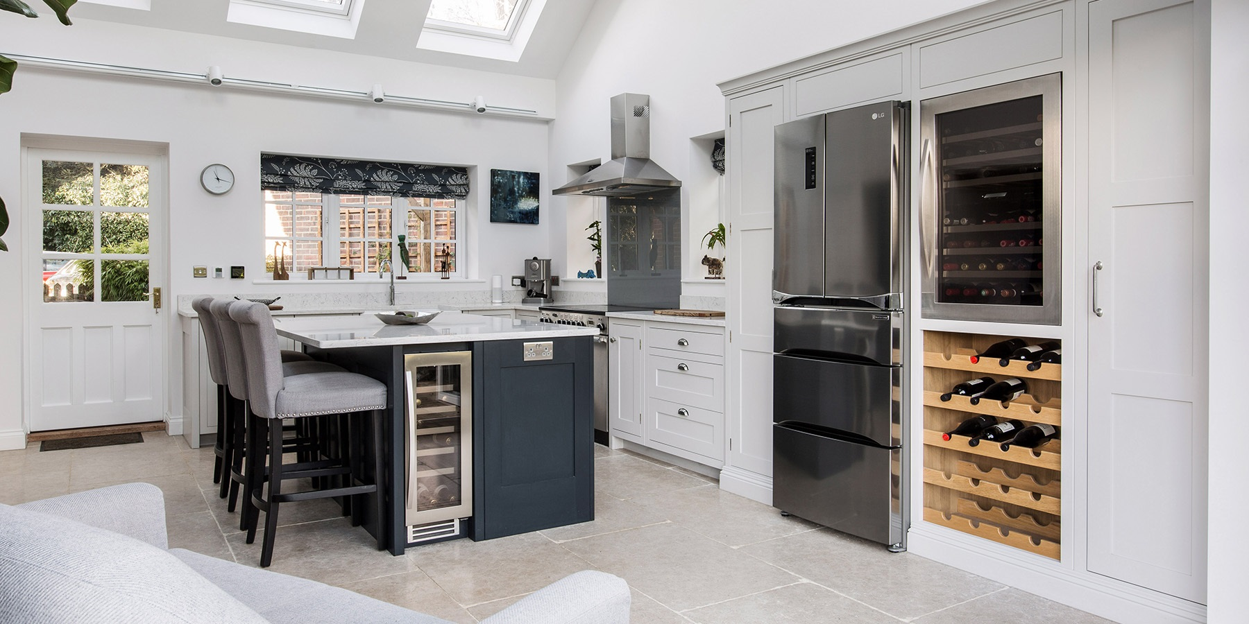 Handmade Shaker Kitchen Extension - Burlanes bespoke Hoyden kitchen cabinetry in white and blue, with central kitchen island with wine cooler and breakfast bar.