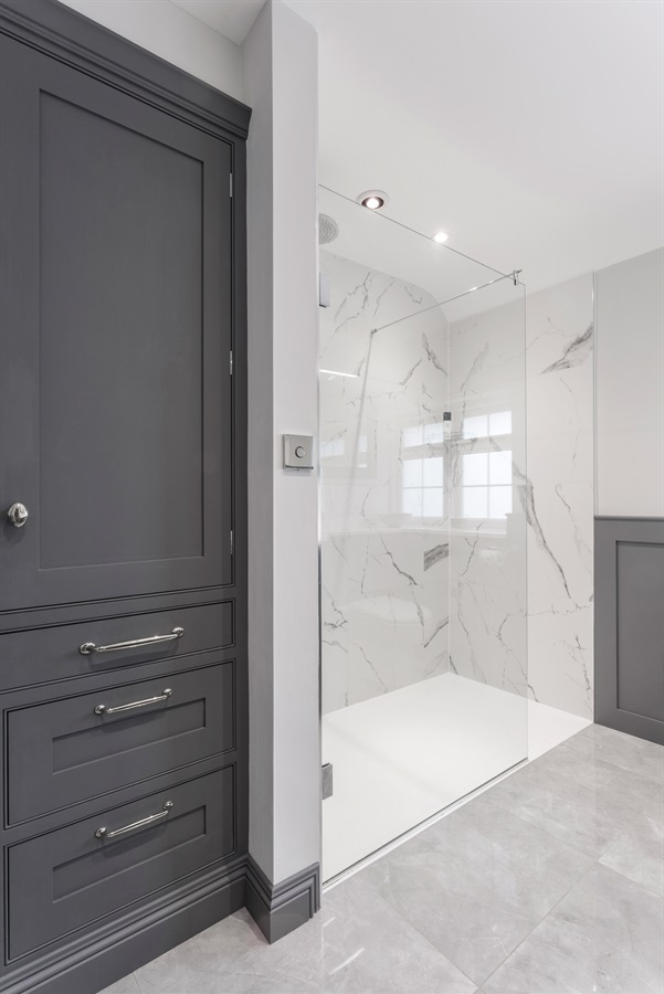 Bespoke Luxury Bathroom Design - Burlanes handmade grey bathroom storage unit and open walk-in shower area with marble tiles and glass shower screen.