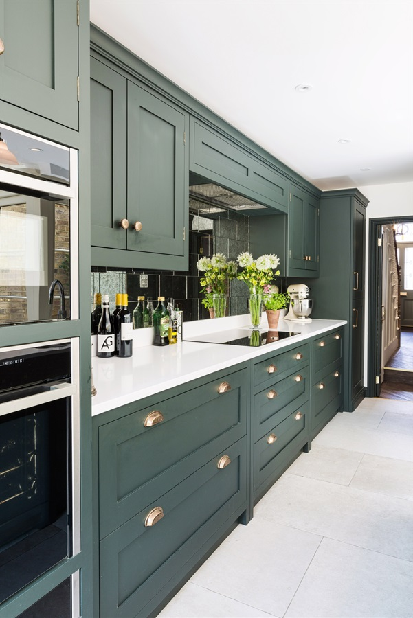 Bespoke Town House Kitchen - Burlanes handmade Hoyden kitchen handpainted in Farrow & Ball 'Studio Green', with white worktops and bronze cup handles.
