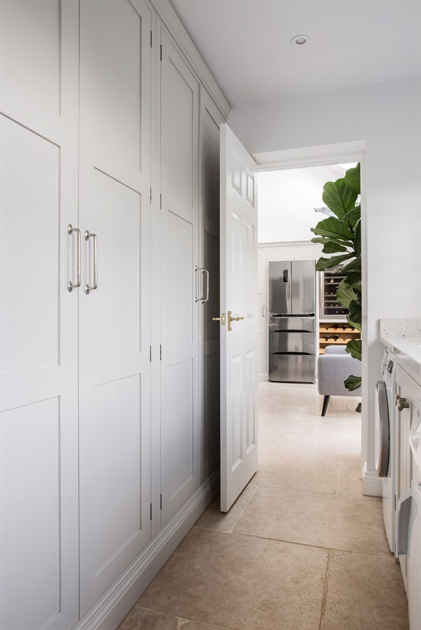 Luxury Bespoke Utility Room - Floor-to-ceiling storage and beautiful handmade utility room cabinetry in white.