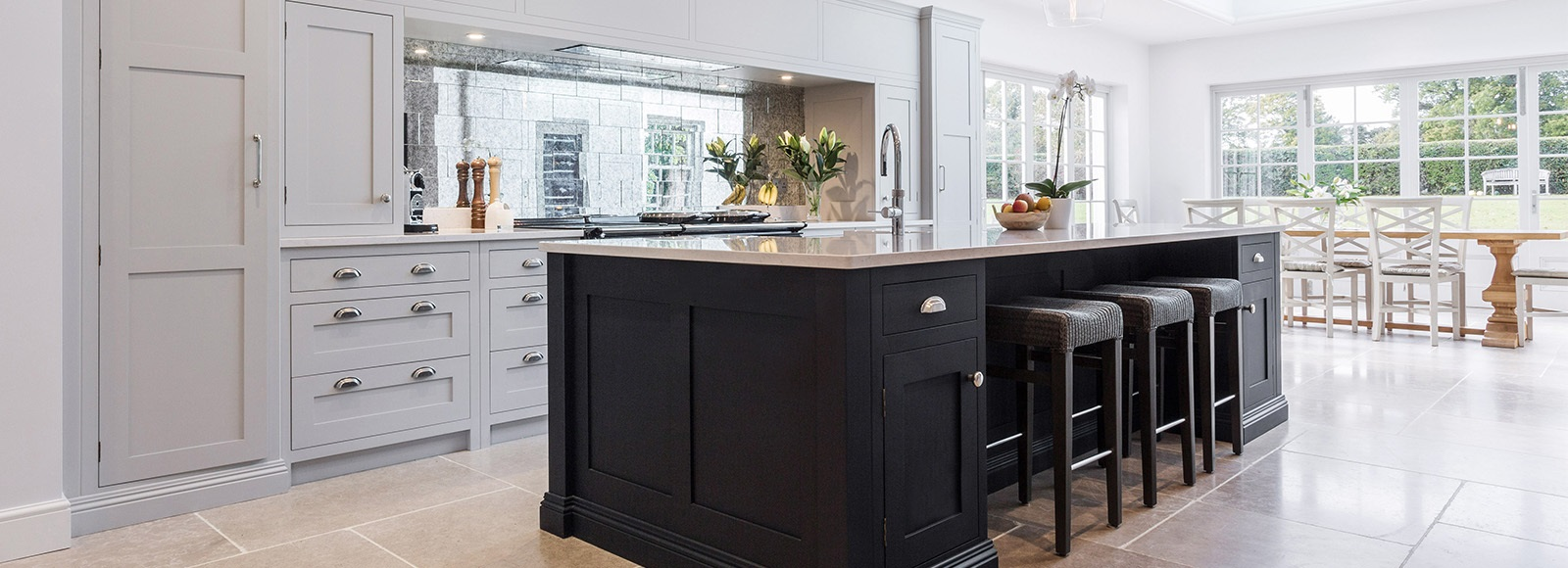 Luxury Open Plan Shaker Kitchen - Burlanes bespoke Wellsdown kitchen in navy and grey, with large central island, mirrored splashback and AGA.