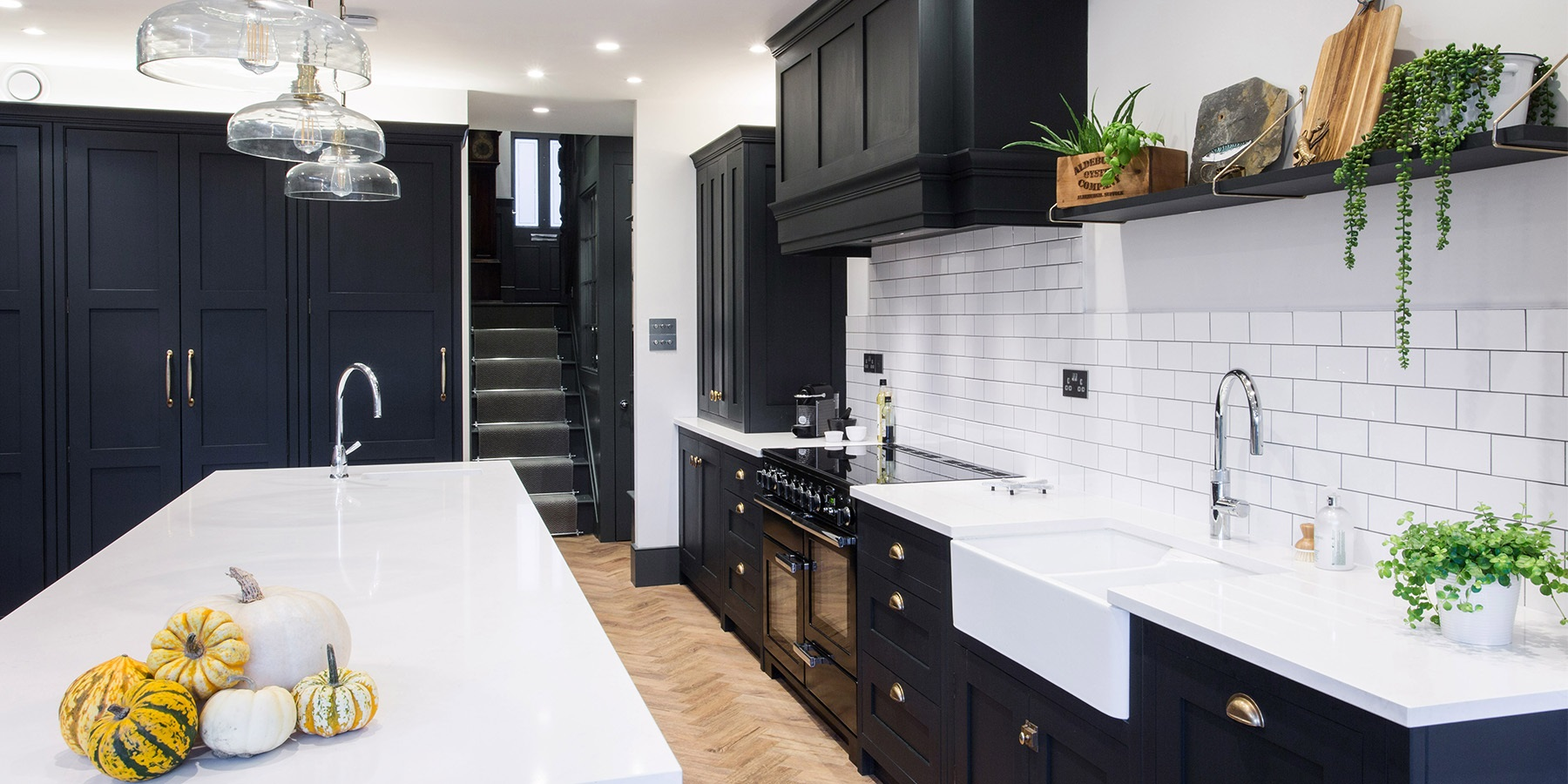 Nautical Themed Industrial Style Shaker Kitchen - Burlanes handmade shaker kitchen with white worktops, contrasting shaker tiles and beautiful greenery.