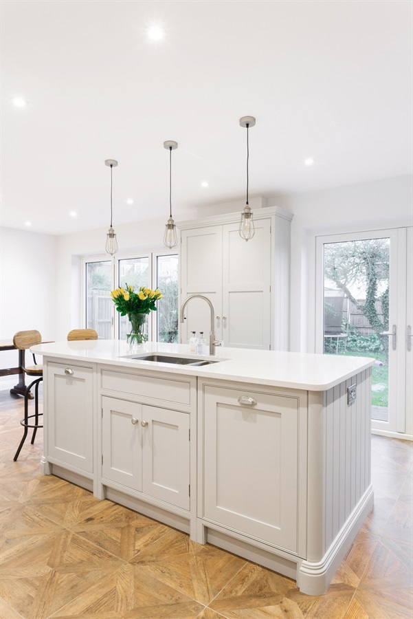 Handmade White Shaker Kitchen - Burlanes bespoke Wellsdown kitchen island with white worktops and larder unit.